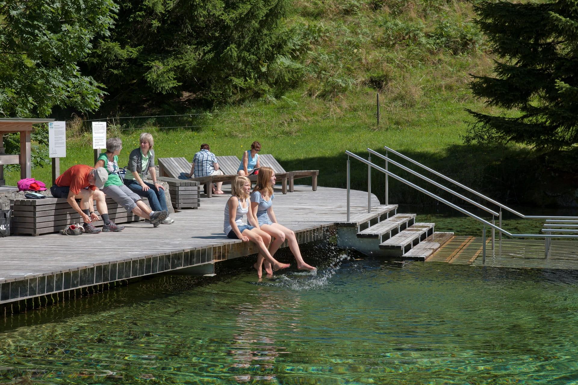 Gäste erfrischen nach einer Wanderung die Füsse im Schwandalpweiher der Kneippanlage Flühli.