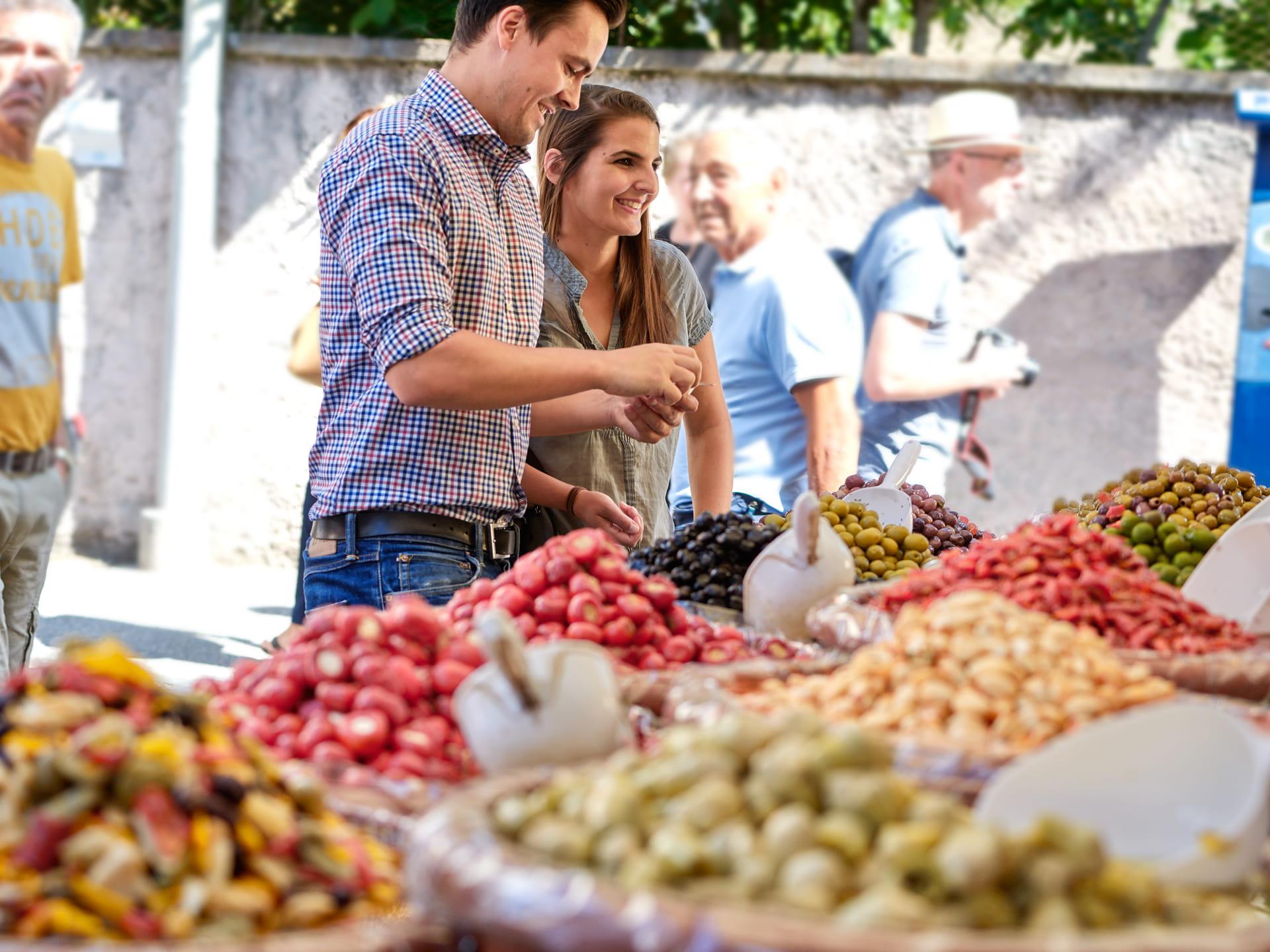 Ein junges Paar verhandelt mit dem Verkäufer über den Preis der Antipasti.