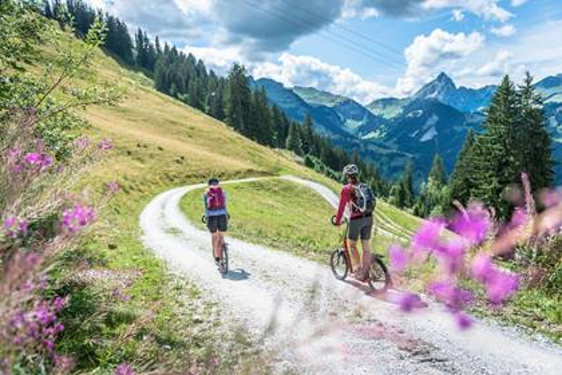 Zwei Frauen fahren mit dem Trottinett einen Weg hinab.