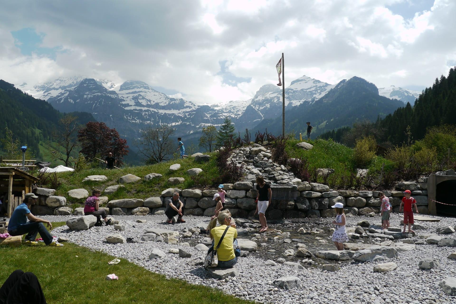 Kinder spielen am künstlichen Bächlein auf dem AlpKultur Spielplatz