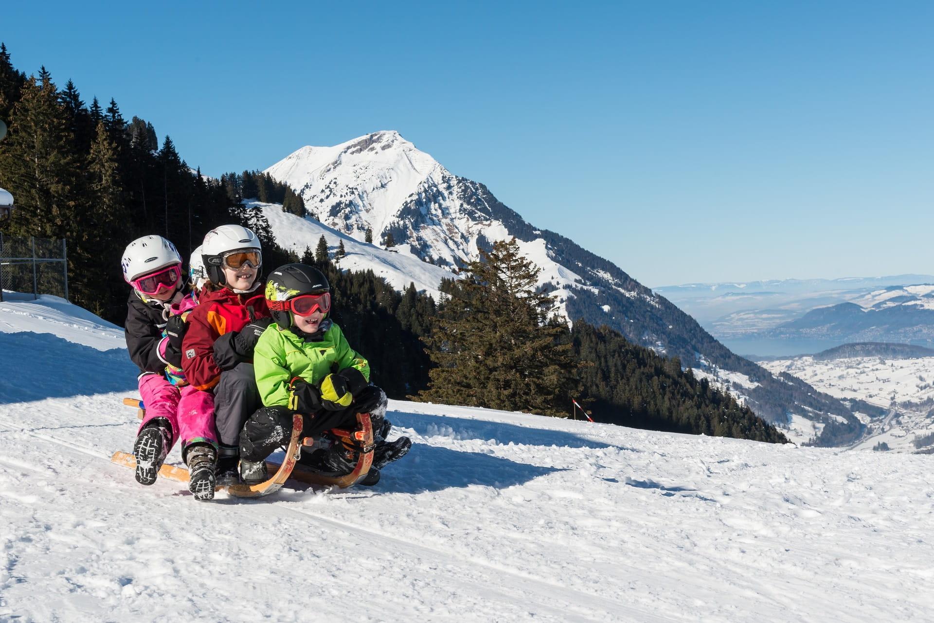 Drei Kinder auf einem Schlitten fahren die Piste herunter in Kiental bei Kandersteg